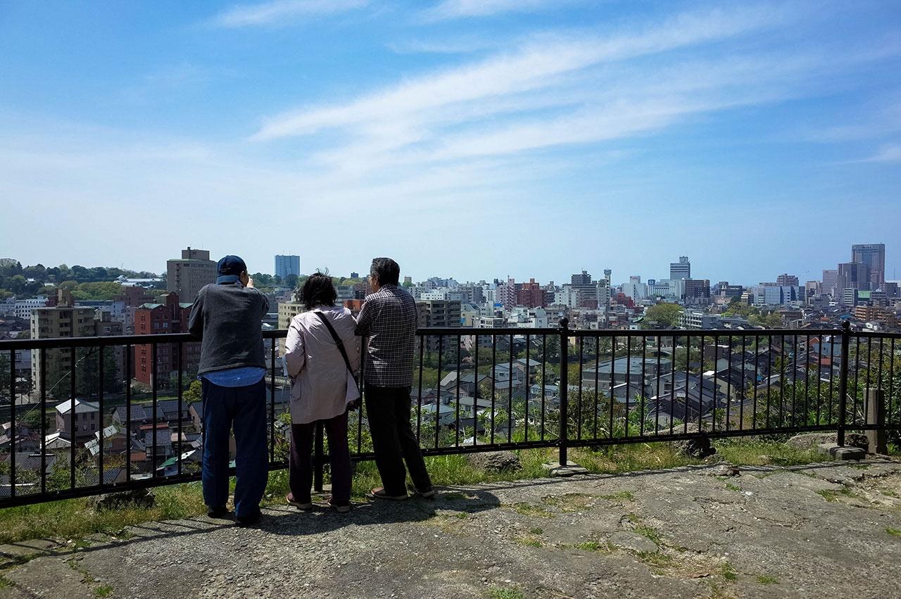 井手さん夫妻(右)に金沢の地形について説明する壺中人さん=宝泉寺で