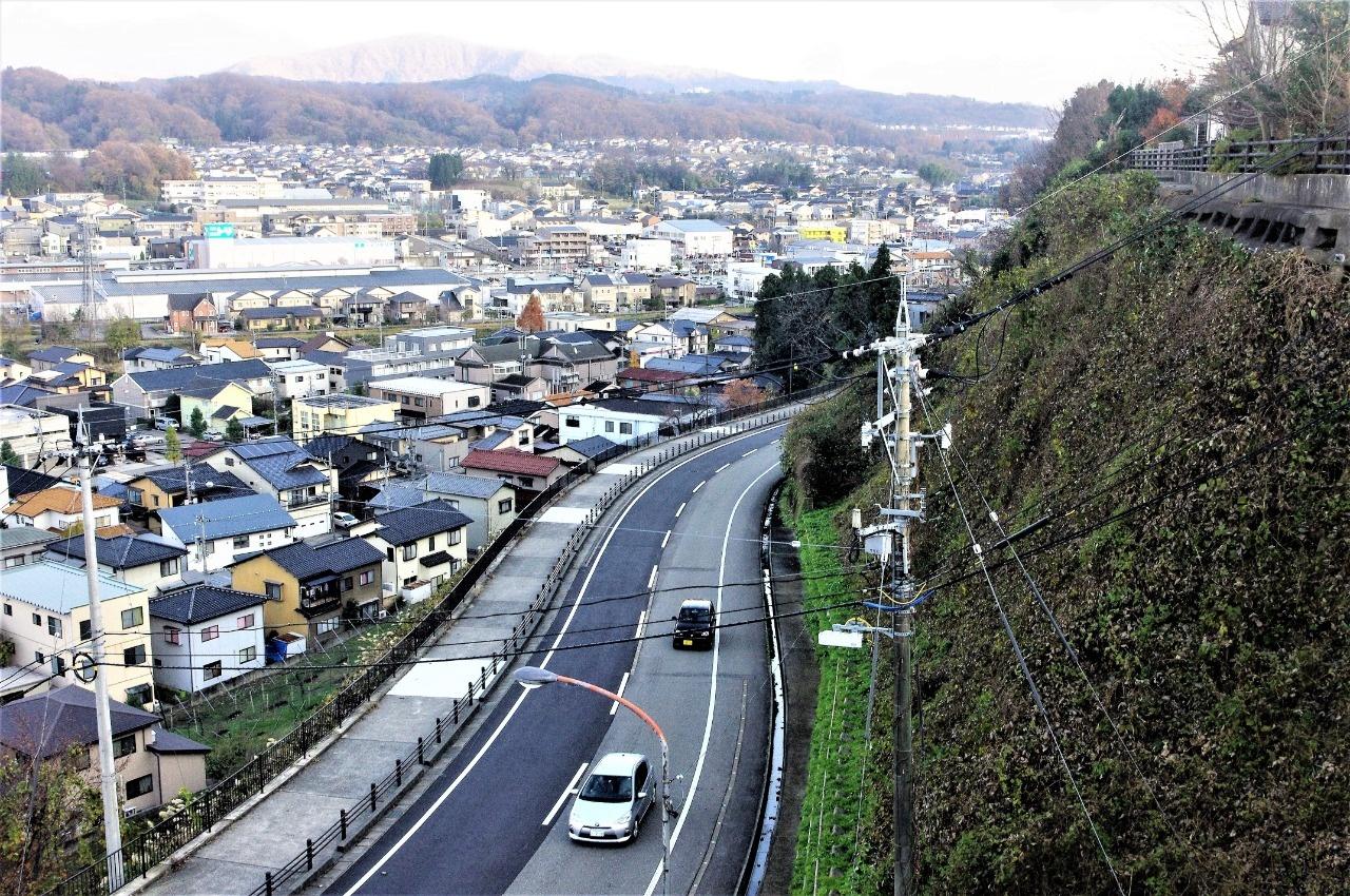野坂上の台地から望む旭坂と、奥にかすむ戸室山